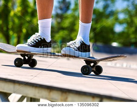Legs skateboard close up in skatepark. Low section of child legs skate on skateboard.