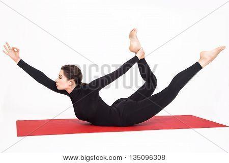 Beautiful athletic girl in black suit doing yoga. Naukasana asana boat pose. Isolated on white background.