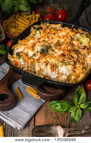 Baked pasta with broccoli, cauliflower, cheese and bechamel sauce in a frying pan on wooden background
