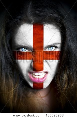 Portrait of a woman with the flag of the England painted on her face.
