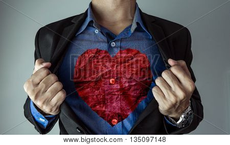 a guy in suit opening his suit showing red crumpled heart shape