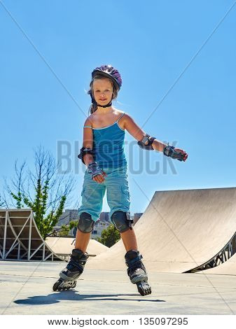 Girl wearing roller skates helmet riding on roller skates in skates park.