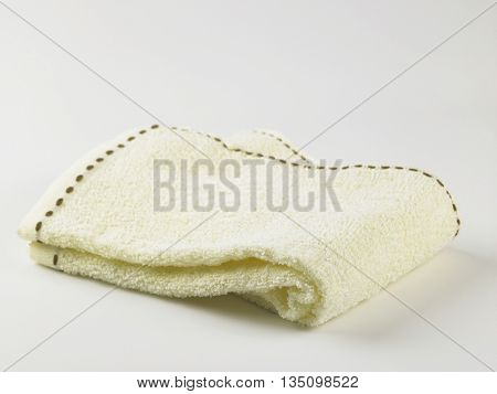 folded yellow towel on the white background