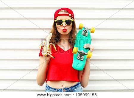 Fashion pretty cool woman with skateboard and banana over white background