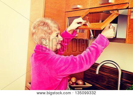 Smile senior woman taking mug from a kitchen cabinet
