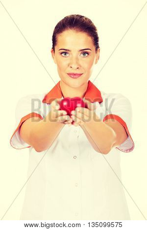 Young female doctor or nurse holding toy heart
