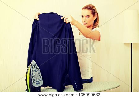 Young woman ironing man's jacket on ironing board