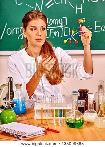 Chemistry female teacher with chemistry test-tube at classroom.