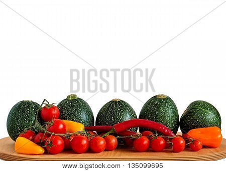 Selection of eight ball zucchini cherry tomatoes chili peppers and yellow orange and red peppers on a wooden board isolated on white.