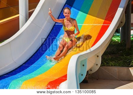 Child teenager wearing bikini slides on water slide and shows thumb up at aquapark . Slide painted in colorful stripes. Summer water park holiday. Outdoor.