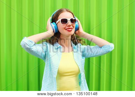 Happy pretty cool woman listens to music in headphones over green background