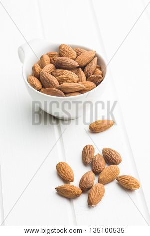 Dried almonds in bowl on white table.