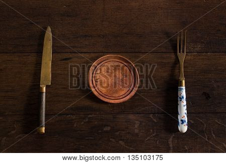 Empy plate with fork and knife, wooden table