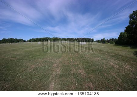 Fisheye photo of public soccer fields with green grass and goals.