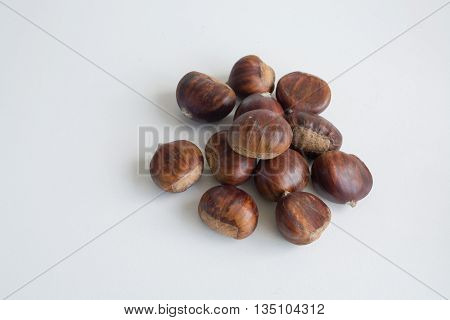 A pile of sweet edible chestnuts on white background