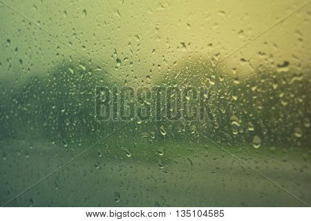 drops of summer rain flowing down the window glass
