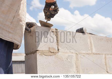 worker aligns with a spatula lay brick cinder blocks.