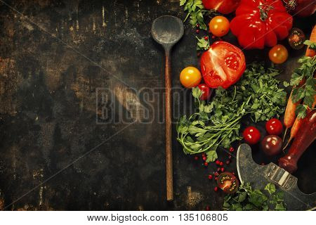 Wooden spoon and ingredients on dark background. Vegetarian food, health or cooking concept.