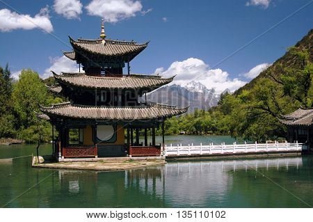 Water pagoda on a small island in Black Dragon Pool Park with Jade Dragon Snow Mountain in the distance