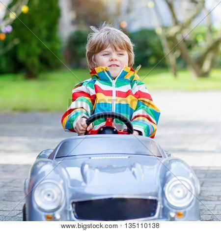 Little toddler boy driving big toy old vintage car and having fun, outdoors. Active leisure with kids outdoors  on warm spring or autumn day.