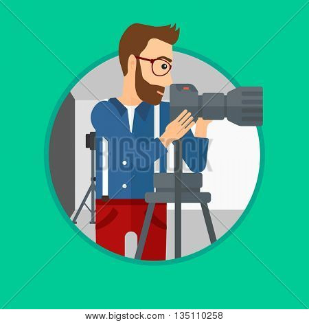 A hipster photographer with the beard working with camera on a tripod in photo studio. Photographer using camera in the studio. Vector flat design illustration in the circle isolated on background.