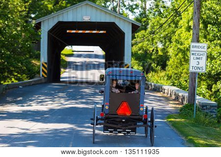 Paradise PA - June 19 2016: Old Oder Amish children look out the rear of a horse-drawn buggy as it enters a traditional covered bridge in rural Lancaster County Pennsylvania.