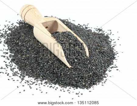 Organic unpeeled black sesame seeds. Black sesame seeds in wooden spoon. Sesame seeds on white background.