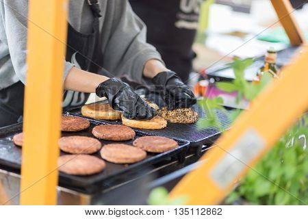 Chef making beef burgers outdoor on open kitchen international food festival event. Street food ready to serve on a food stall.