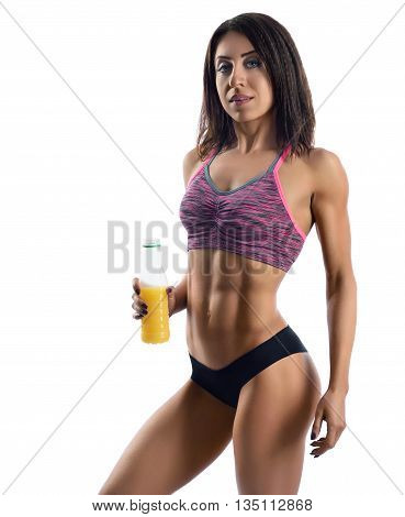 Vital energy. Studio shot of a beautiful female fitness model posing in her sportswear showing off her muscular body holding a bottle of juice isolated on white