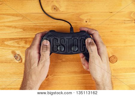 Hands using gamepad controller on wooden desk flat lay top view gaming and entertainment concept