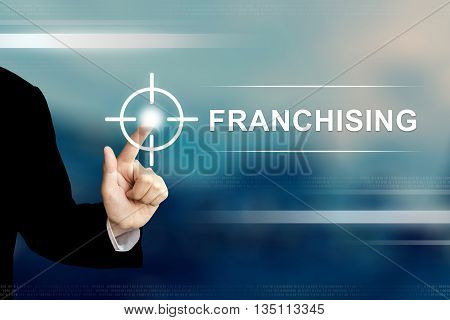 business hand pushing franchising button on a touch screen interface