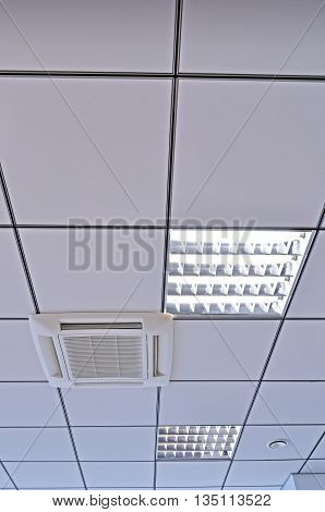 Lamps with fluorescent lights smoke detectors and ventilation system on the suspended ceiling closeup view