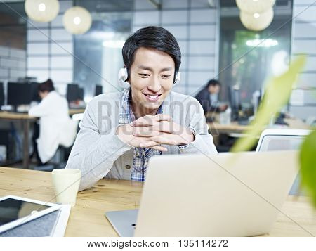 young asian designer looking at laptop computer while listening to music with headphones in office.