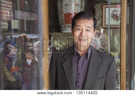 Asian small business owner in front of store