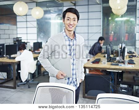 confident young asian entrepreneur standing in own company with laptop computer looking at camera smiling.