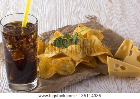 Potato chips, cheese with soda on wooden background