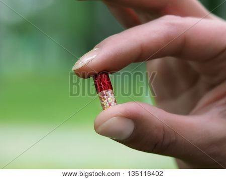 Pill capsule with colored beads in a female hand. Background nature green grass. Concept - medicines homeopathy
