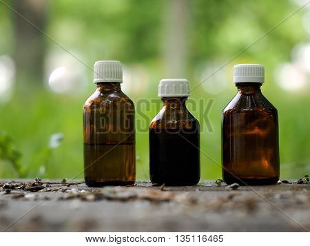 Three medical bottle of dark glass. Natural background - trail grass. Concept - medicines based on herbs aromatherapy homeopathy