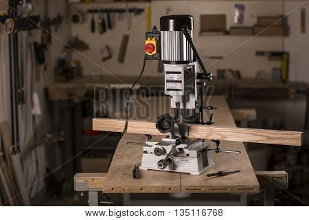 Mortiser machine on the wooden workbench in carpentry