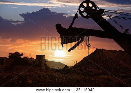 Shovel dipper. Dump Truck carries ore. Sunset.