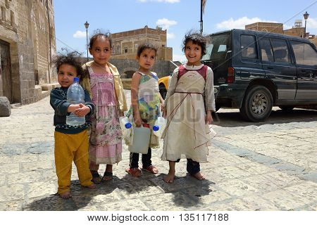 YEMEN SANAA - MAR 6 2010: Unidentified little local girls with empty water-pots going in search of drinking water in Sanaa. Among other arabic countries in 2012 Yemen became a site of civil conflicts