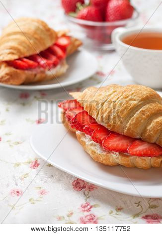 croissant with fresh strawberries ricotta (cottage cheese) for breakfast on a wooden background