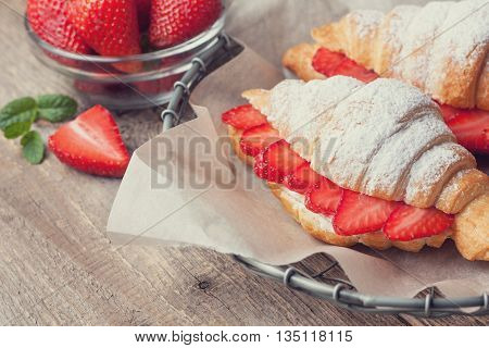 croissant with fresh strawberries ricotta (cottage cheese) for breakfast on a wooden background. Toning