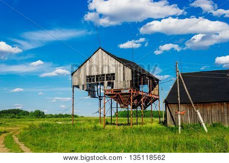 Old ruined abandoned grain elevator in the field