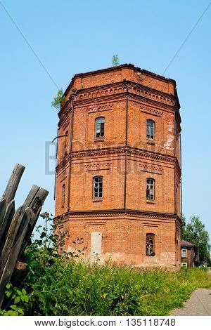 Old red brick water tower on a summer day