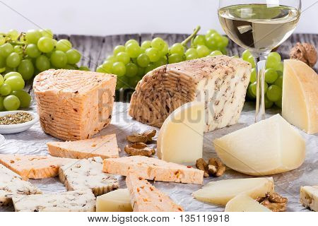 wineglass with cold white wine and organic homemade goat cheese with walnuts and spices. Green Grapes and walnuts on parchment paper studio lights view from above close-up