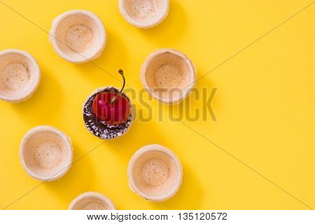 Delicious chocolate tartlets with one cherry, chocolate and coconut on yellow background
