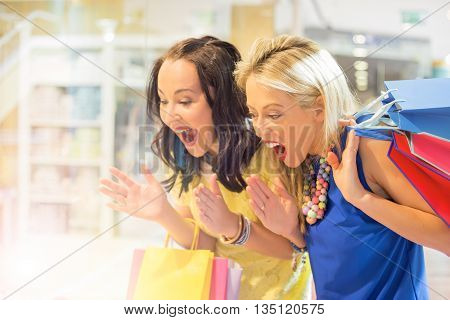 Excited women at the shopping center window shopping