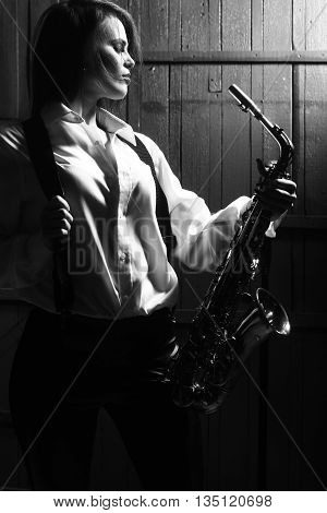 young pretty woman with sexy stylish cloth playing saxophone in retro braces and pants with shirt black and white