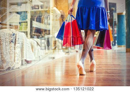 Female shopping in shopping center with many bags